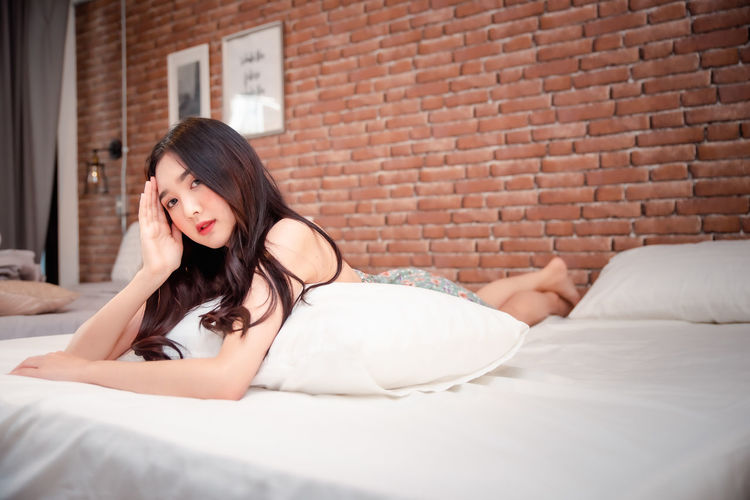 Young woman lying down on bed