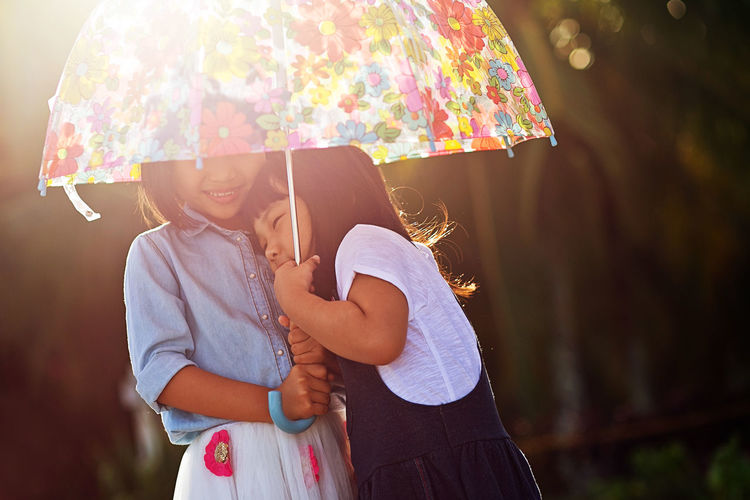 Close-up of sisters with umbrella standing outdoors