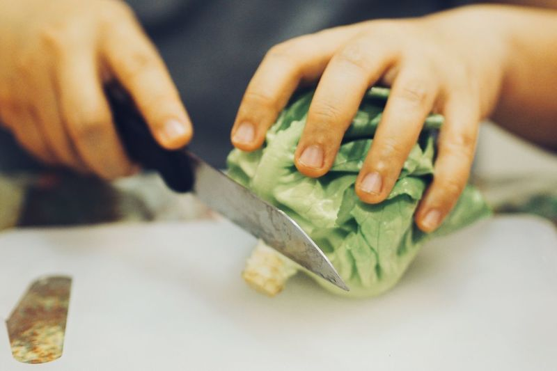 Close-up of person cutting vegetable on table