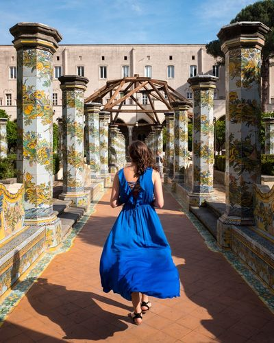 Rear view of woman walking amidst columns with floral pattern