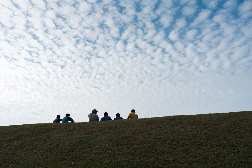Mal workers sitting and chatting on grass field under dreamy cloudy sky after work. Dreams Relaxing Sitting Workers Young Chatting Cloud - Sky Clouds Future Grass Field Guys Many Men People Real People Sky Talking Togetherness