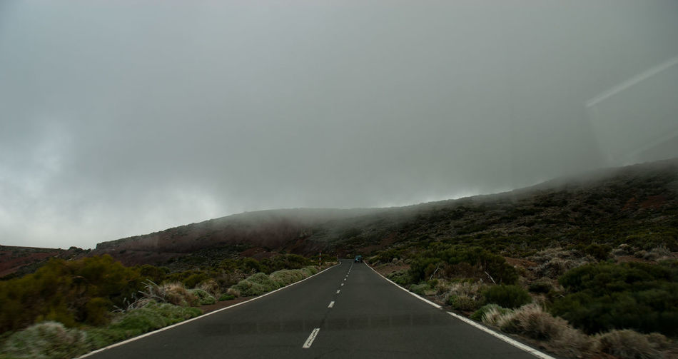 Road leading towards mountain against sky