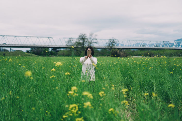 Woman on grassy field against cloudy sky