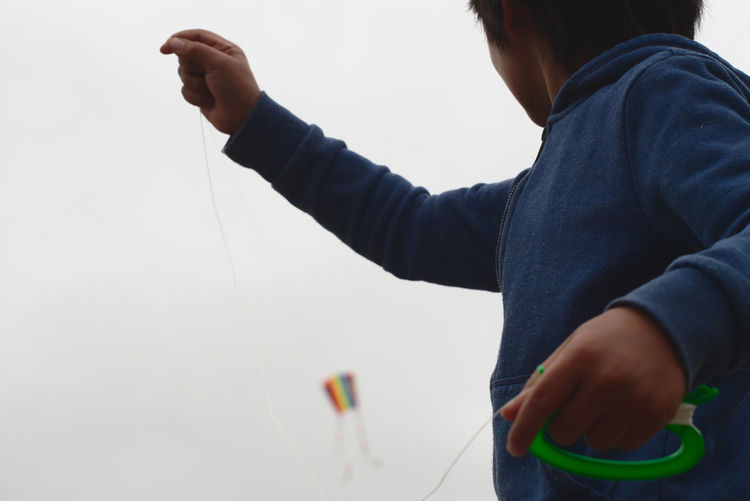 Low angle view of boy flying kite in sky