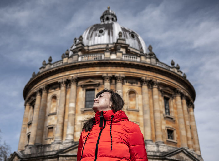 Low angle view of woman standing against cathedral