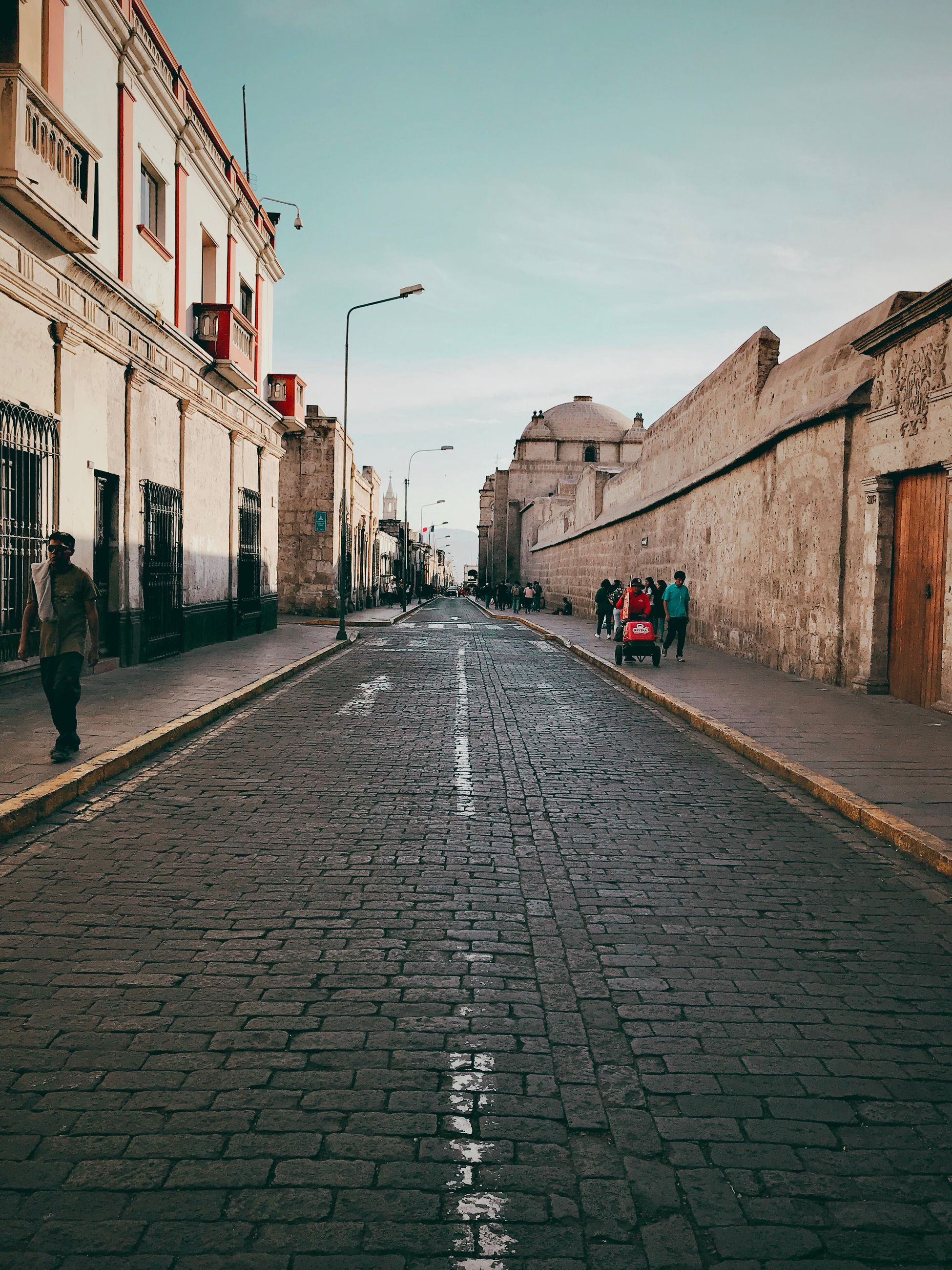 architecture, building exterior, built structure, the way forward, street, city, direction, real people, group of people, sky, footpath, incidental people, men, lifestyles, cobblestone, day, women, nature, sidewalk, diminishing perspective, outdoors, paving stone