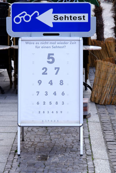 Public outdoor eyesight test board Doctor  Examination Glasses Read Blue City Commercial Sign Communication Day Eyesight Test Germany Guidance Health Information Medical No People Number Optician Outdoors Sidewalk Sign Symbol Testing Text Vision