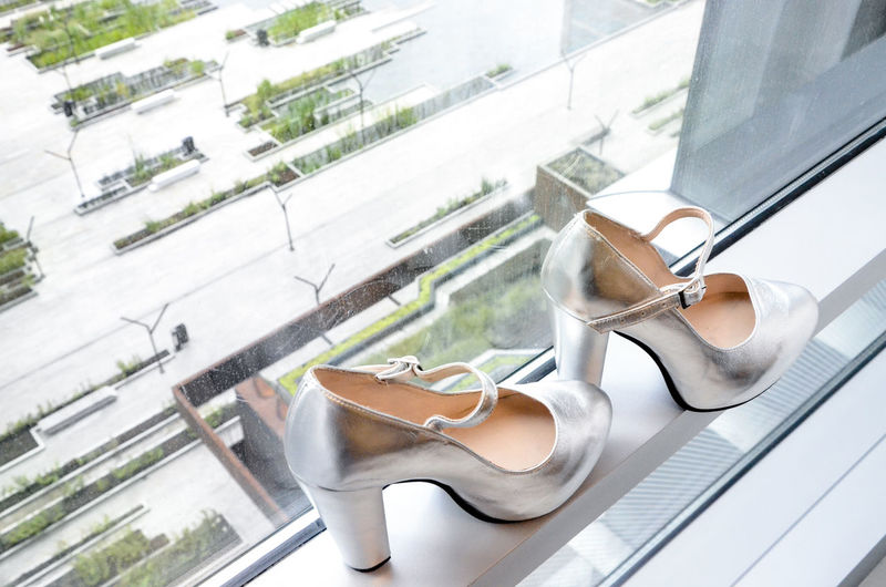High angle view of silver high heels on window sill