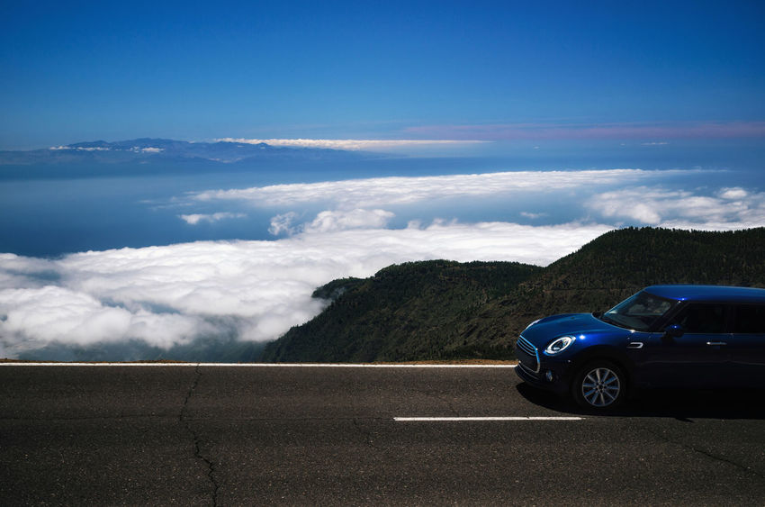 Dark car travel on the mountain serpentine over clouds along the precipice of Tenerife against the sky. Roadtrip around the Canary islands Canary Islands Cloods Above The Clouds Beauty In Nature Blue Car Cloud - Sky Day Land Vehicle Nature Outdoors Road Roadtrip Sky Tenerife Tenerife Island Transportation Mobility In Mega Cities Go Higher