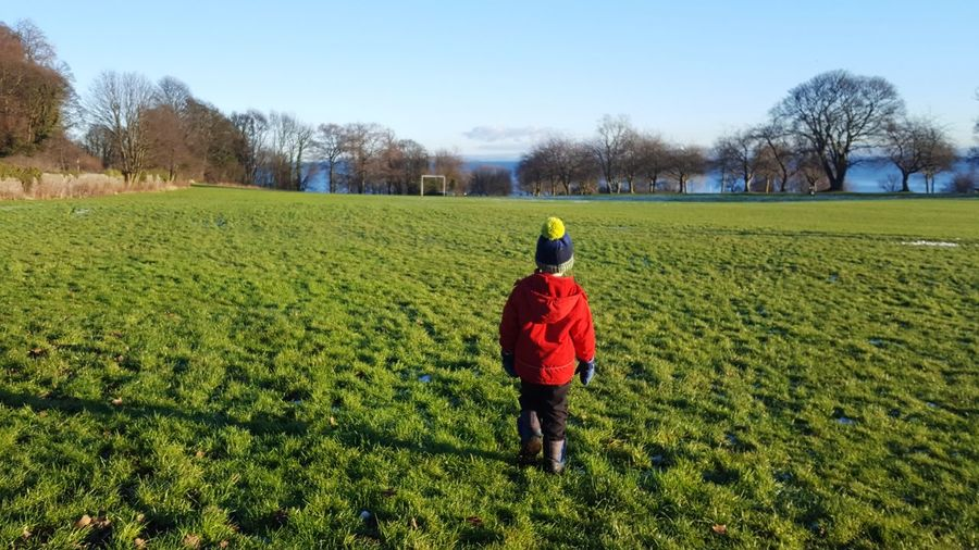 Rear view of child walking on grassy field during sunny day