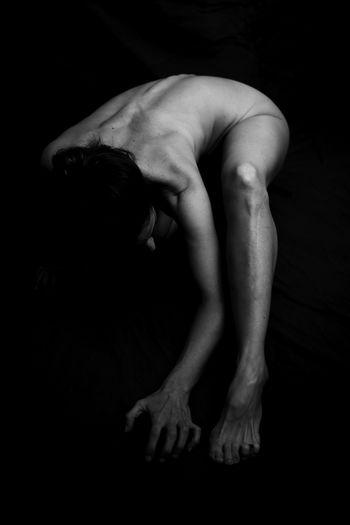 Full length of naked woman bending against black background