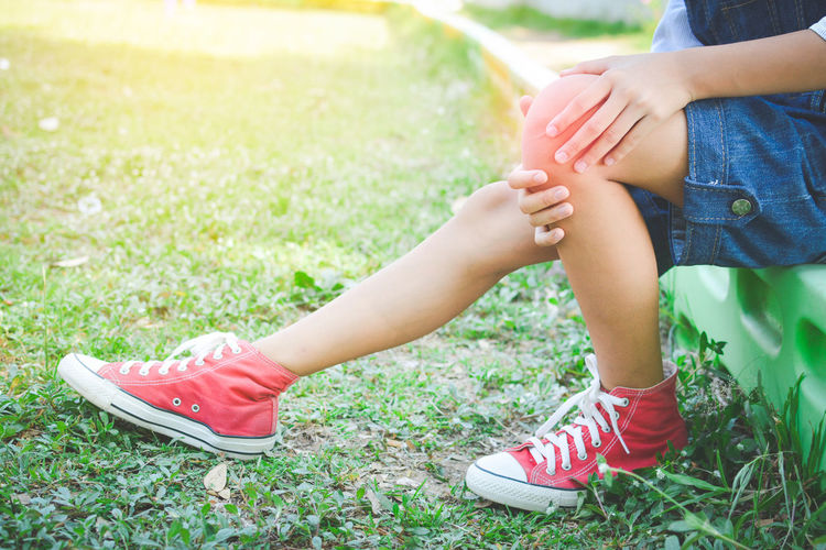 Low Section Of Girl Holding Knee While Sitting At Park