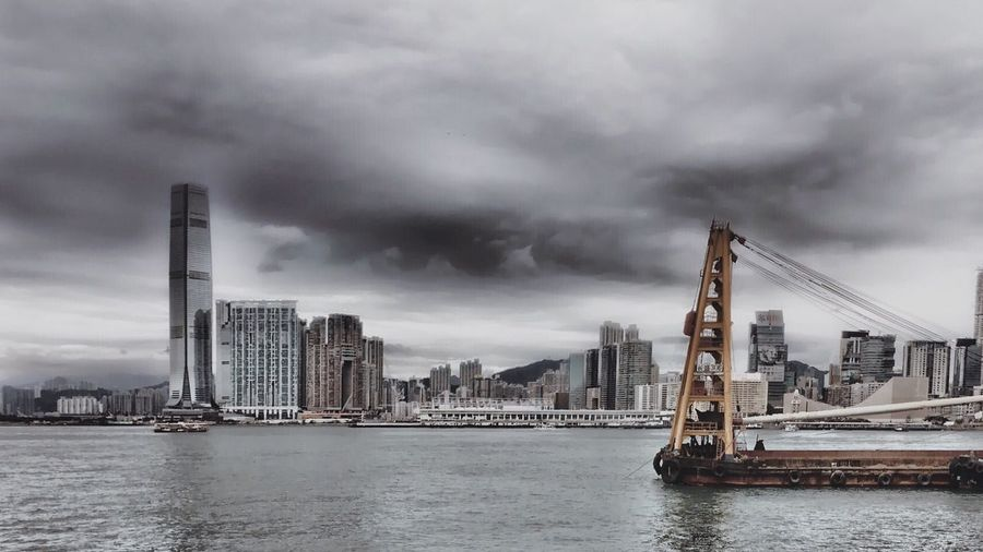 Tugboat Sailing On River By Cityscape Against Cloudy Sky