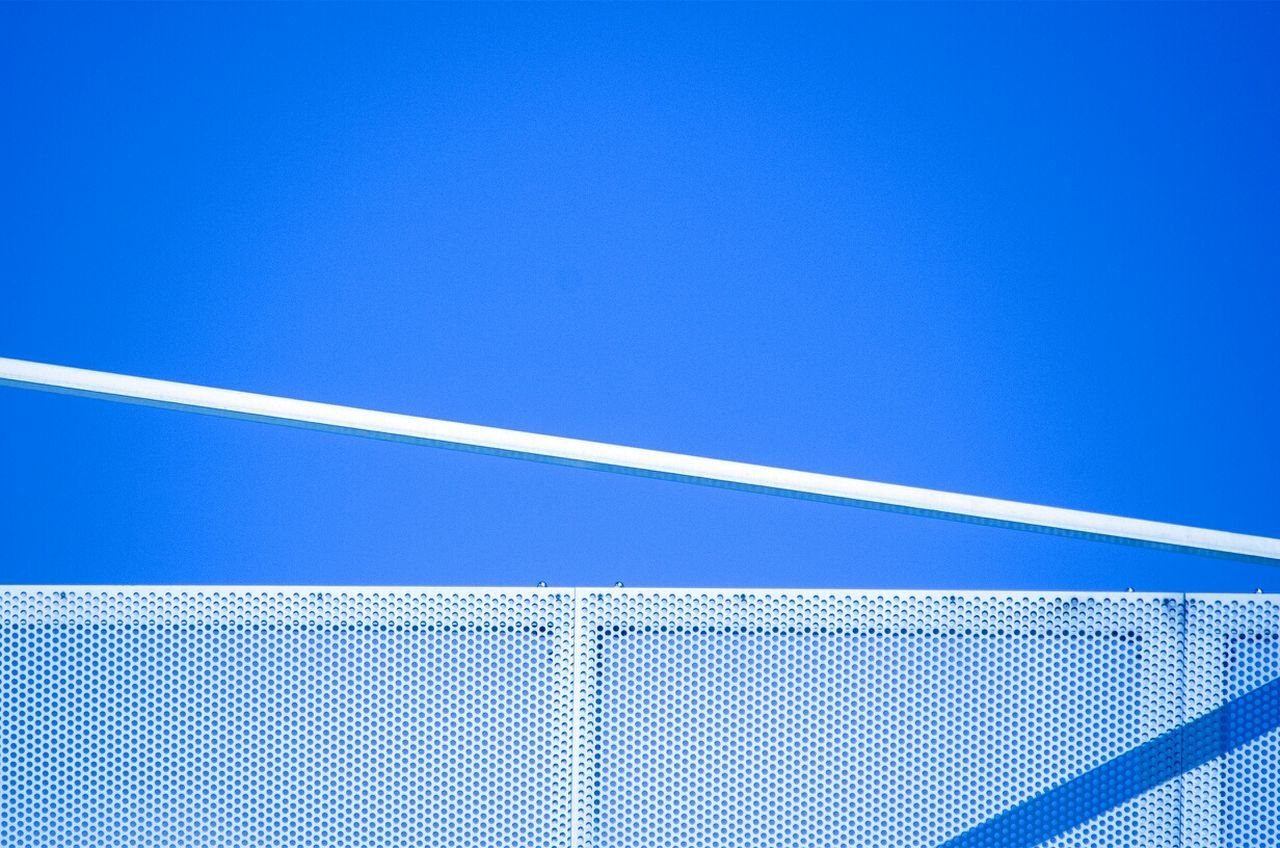 High section of netted wall against clear blue sky