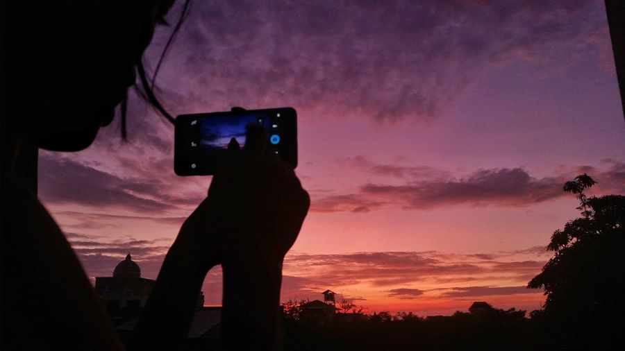 Silhouette person photographing camera at sunset