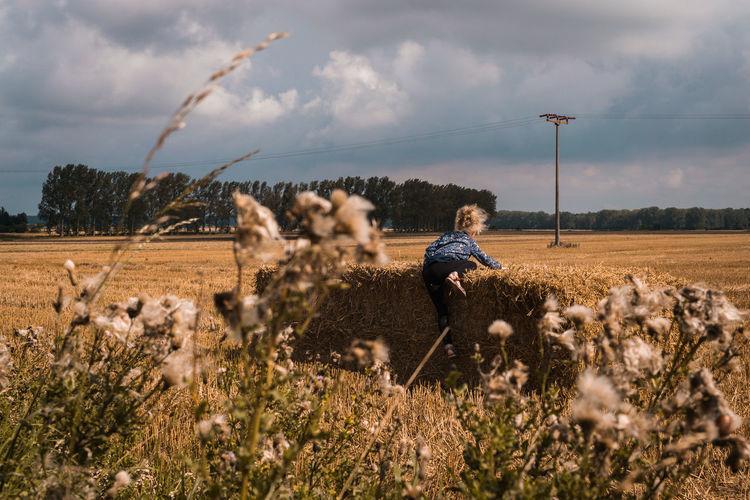 Girl Climbing On Hay Bale Against Sky