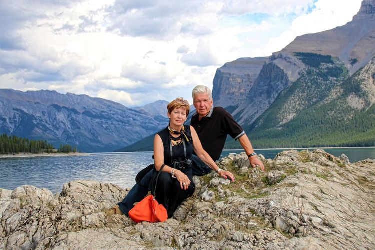 Portrait of couple sitting on rock formation against mountains