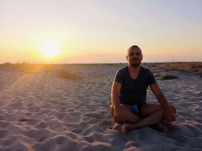 Portrait of mid adult man sitting on beach against sky during sunset