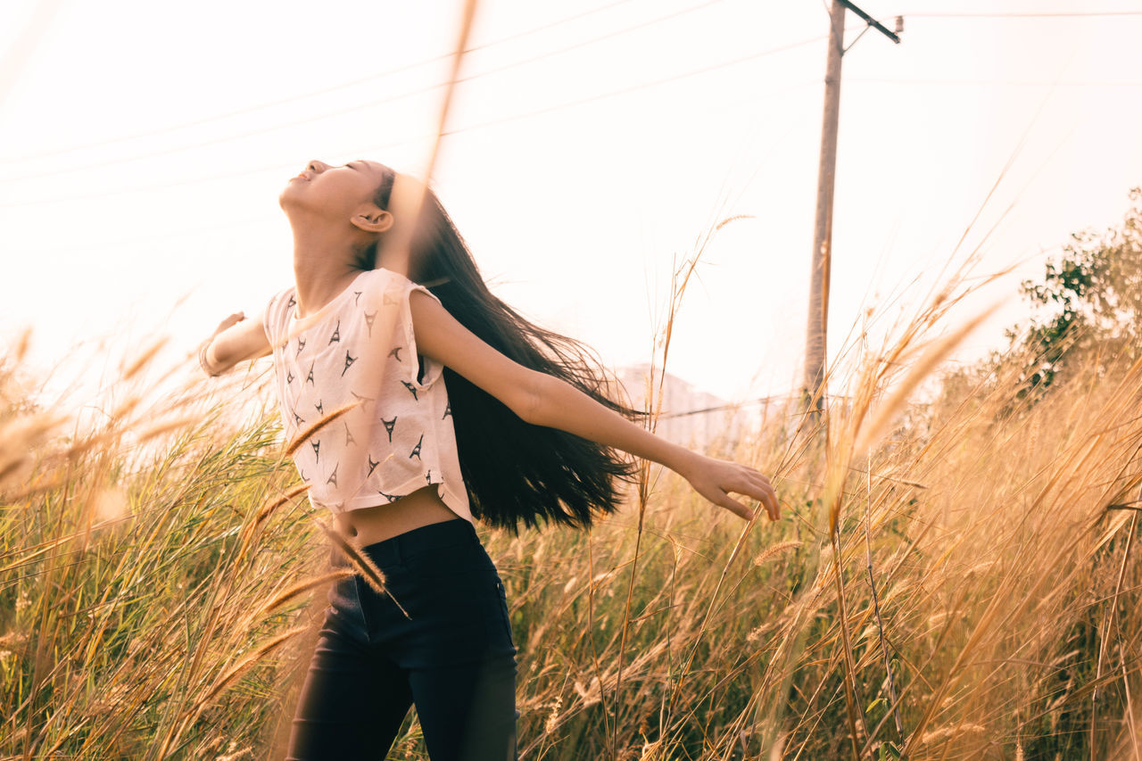 Low angle view of girl standing in grassy field against sky