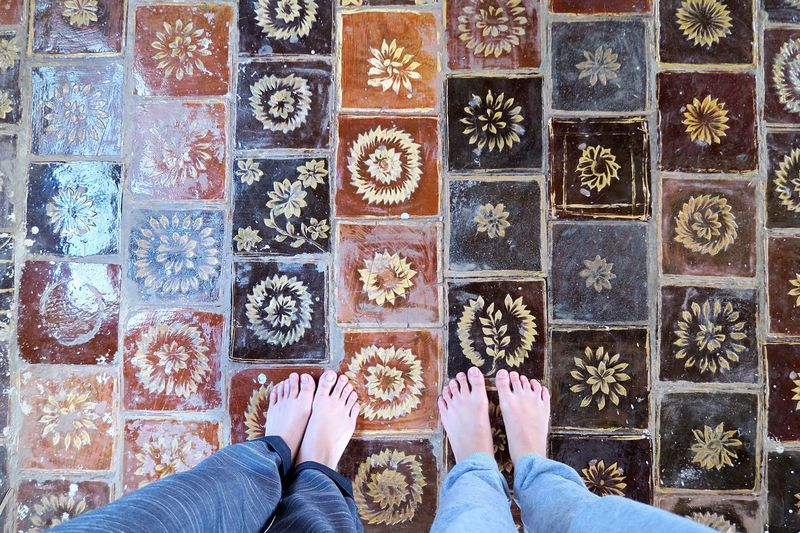 Low section of friends standing on patterned tiled floor