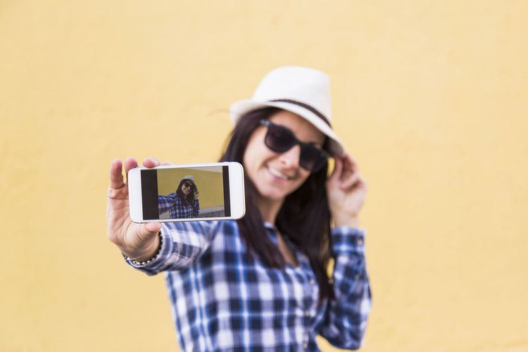 Portrait of young woman photographing with mobile phone