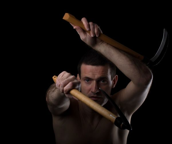 Portrait of shirtless man holding weapons against black background