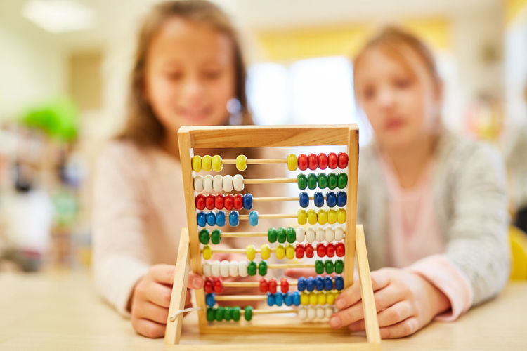 Students using abacus while sitting on table in classroom