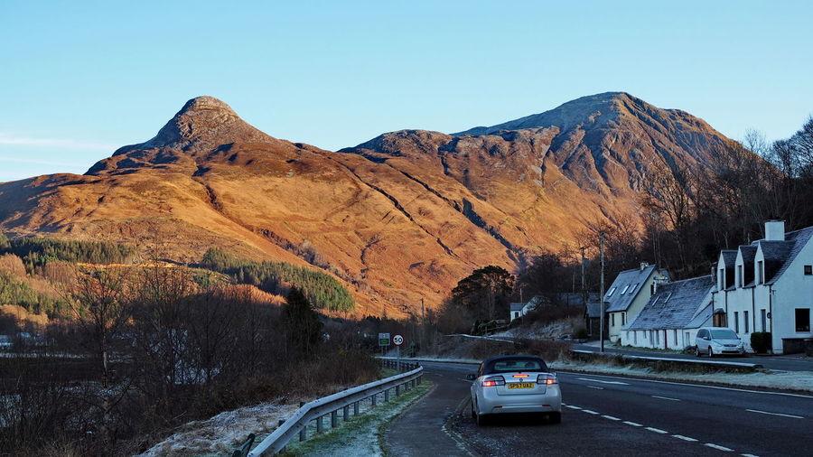 Cars on road against mountain range