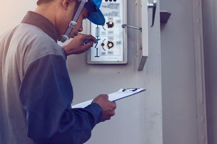 Male engineer checking meter