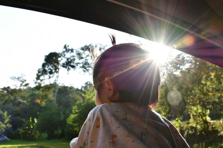 Close-Up Of Baby Girl Looking At View Through Car Window During Sunny Day