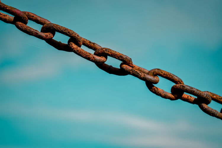 Close-up of rusty chain against blue sky