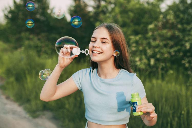 Cute girl making bubble outdoors