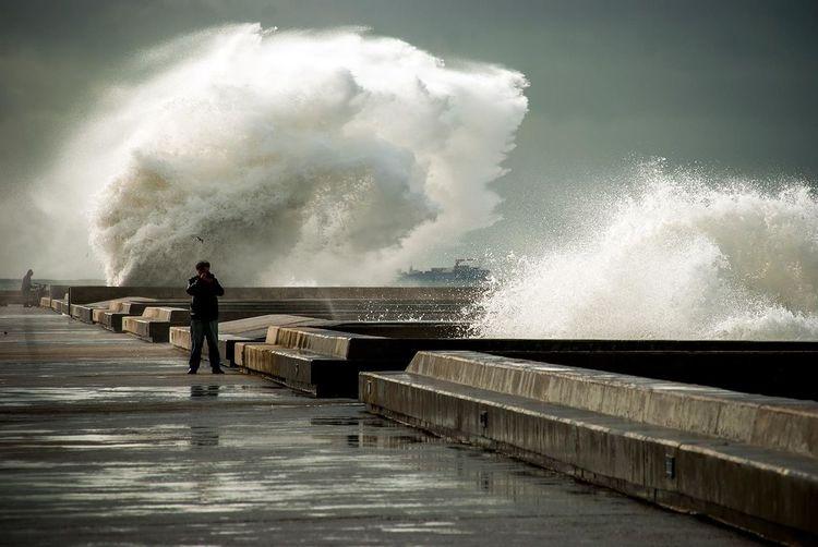 Full Length Of Man Photographing By Water Splashing At Promenade
