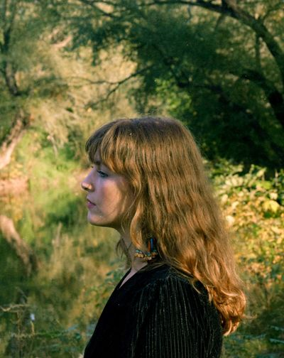 Profile view of woman against trees