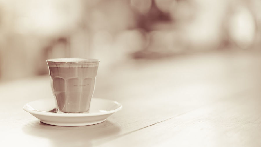small cup of piccolo latte served on wooden table with copy space on right, monotone Bar Barista Beverage Bright Brown Cafe Caffeine Clean Coffee Copy Cup Drink Fresh Glass Hot Latte Milk Monochrome Monotone Piccolo Relax Retro Serve Small Space Table Tone