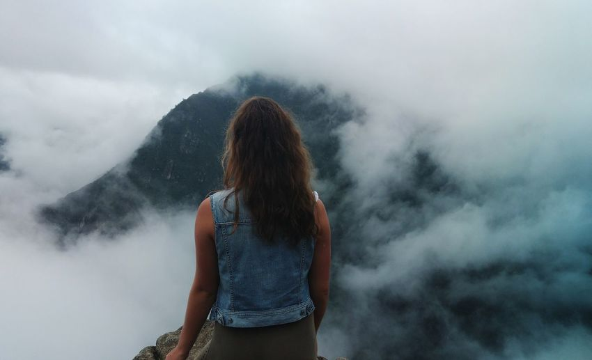 Rear view of woman looking at mountains during foggy weather
