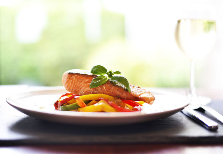 Delicious grilled salmon filet with vegetables on a white food scene with grilled fish and wooden table. Gourmet Dinner Grilled Salmon Salmon Dish Table Setting Wooden Table Basil Leaf Fish Food Food And Drink Freshness Gourmet Gourmet Food Healthy Eating Indoors  No People Plate Ready-to-eat Restaurant Food Salmon Salmon Filet Still Life Summer Food Table Vegetable White Wine