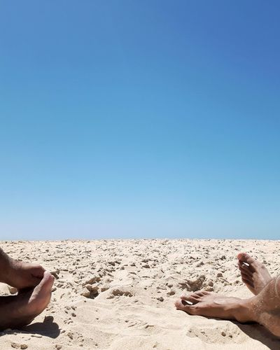 Low section of man lying on sand at beach against clear blue sky