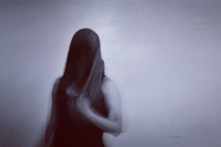 Blurred motion of person standing against wall