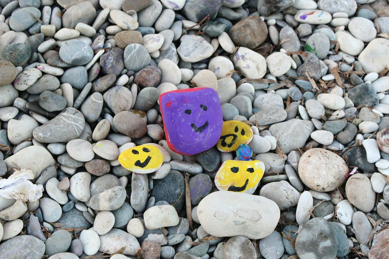 High Angle View Of Smiley Face Painted On Stones