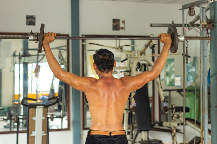 Rear view of shirtless man exercising with dumbbell at gym
