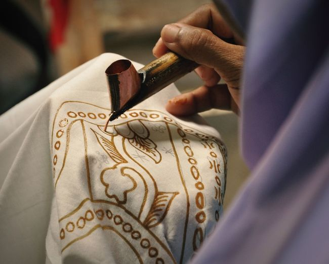 Cropped hand of artisan making design on textile