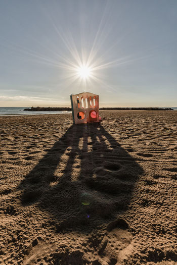 Sunlight falling on sand at beach against sky
