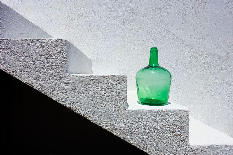 Close-up of green bottle on steps