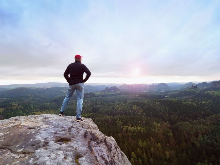 Man in jeans black outdoor sweatshirt and red cap. melancholy misty day in sandstone mountains