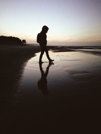 Silhouette man walking on beach against sky during sunset