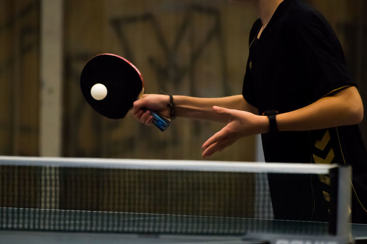 Midsection of woman playing table tennis