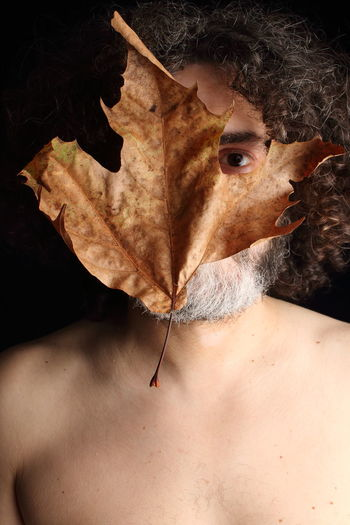 Portrait of shirtless man with autumn leaf on face against black background