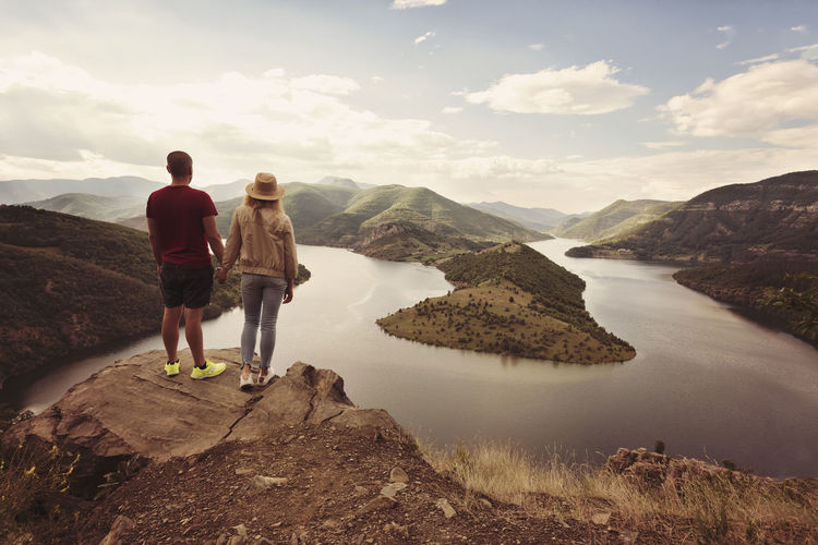 Rear view of couple standing against river and mountains on cliff