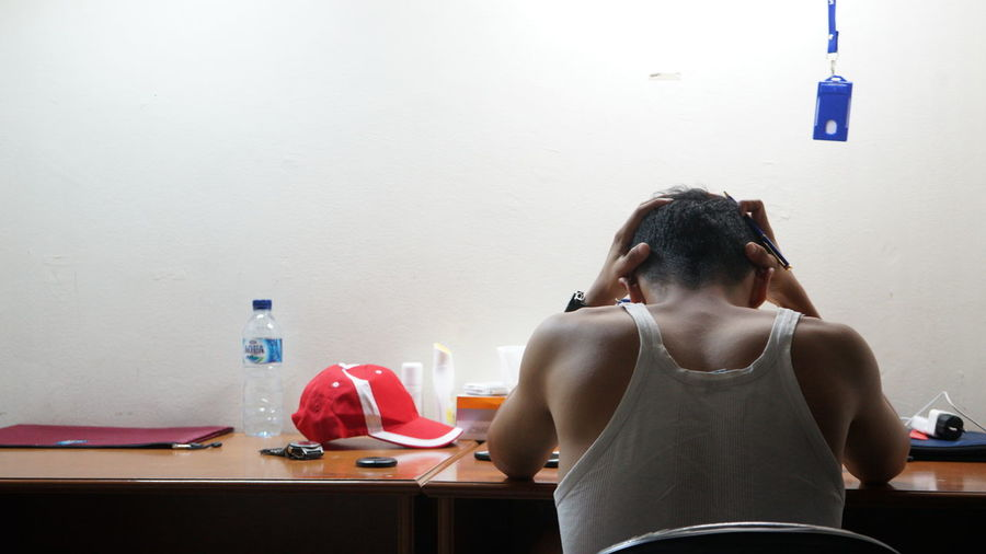 Rear view of woman sitting on table at home